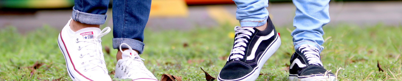 Photo of two young peoples feet with vans and converse.