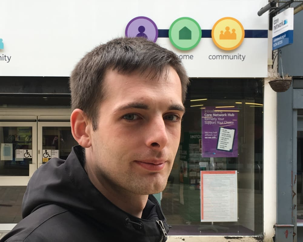 Photo of local young man Dan, in front of Care Network Shop
